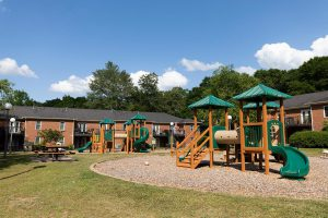 Exteriors of Brandon Oaks apartments playground and picnic area on a spring afternoon.